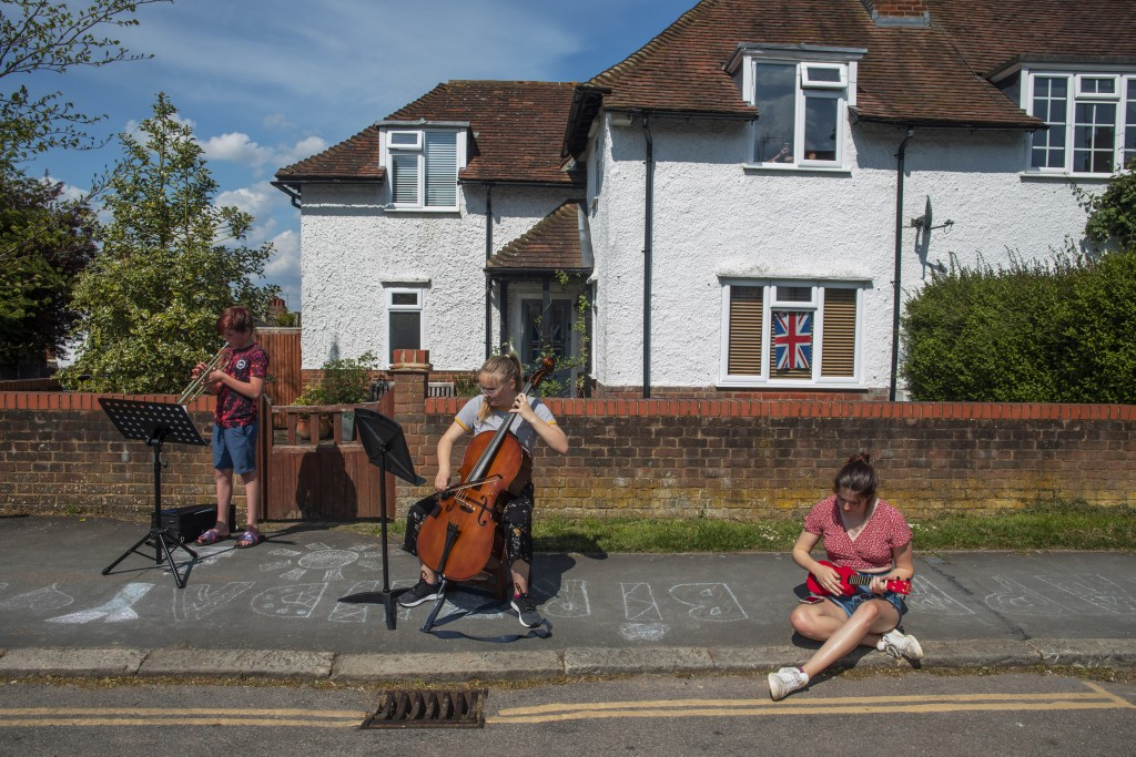 "Neighbors gather to play ""We'll meet again"" for a socially distant concert during Victory in Europe Day celebrations during the coronavirus outbreak i..."
