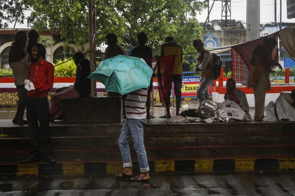 Commuters take shelter in an empty taxi stand at Howrah railway station as it rains in Kolkata, India, Wednesday, May 20, 2020. Amphan, a powerful cyc...