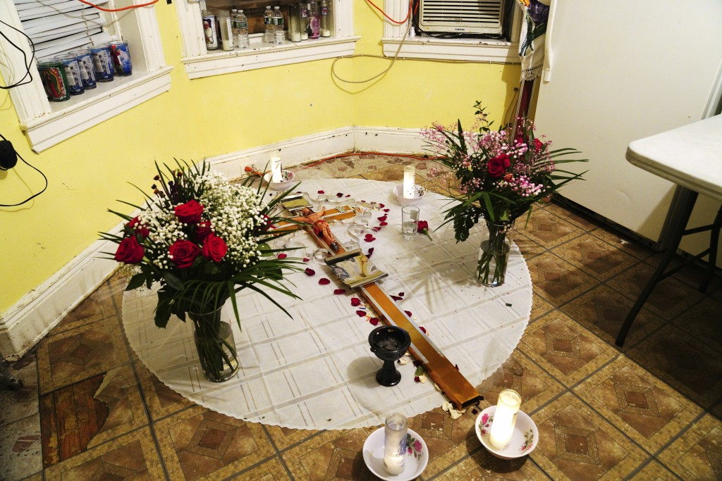 In this May 10, 2020, photo, a makeshift altar is displayed for Reyna Martinez's father, who died of COVID-19, in Martinez's home in the Queens boroug...