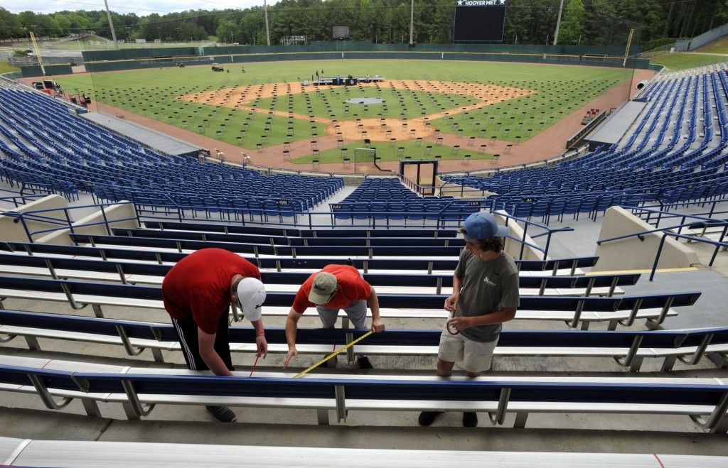 Workers use tape to block off seats as they prepare for a large high school graduation ceremony at Hoover Metropolitan Stadium in Hoover, Ala., Tuesda...