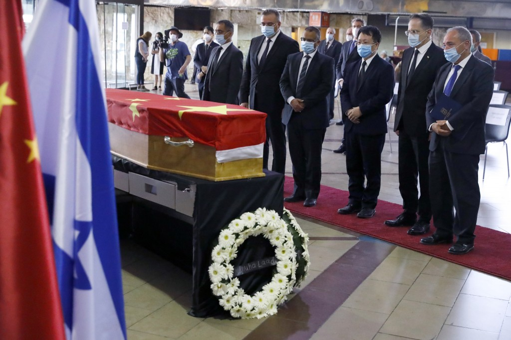 Chinese and Israeli officials pay their respect in front of the flag-draped coffin of Chinese Ambassador Du Wei, who died at his home in the coastal c...