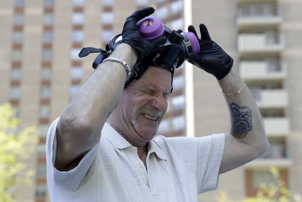 Safety Director Tony Barzelatto reacts as he pulls off his protective mask after disinfecting parts of a building in Co-op City in the Bronx borough o...