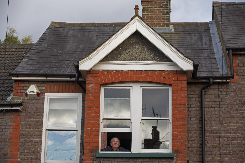 Cristopher Talbot-Ponsonby, a lifetime resident of Berkhamsted, England, looks out of his window during the coronavirus outbreak Thursday, April 2, 20...