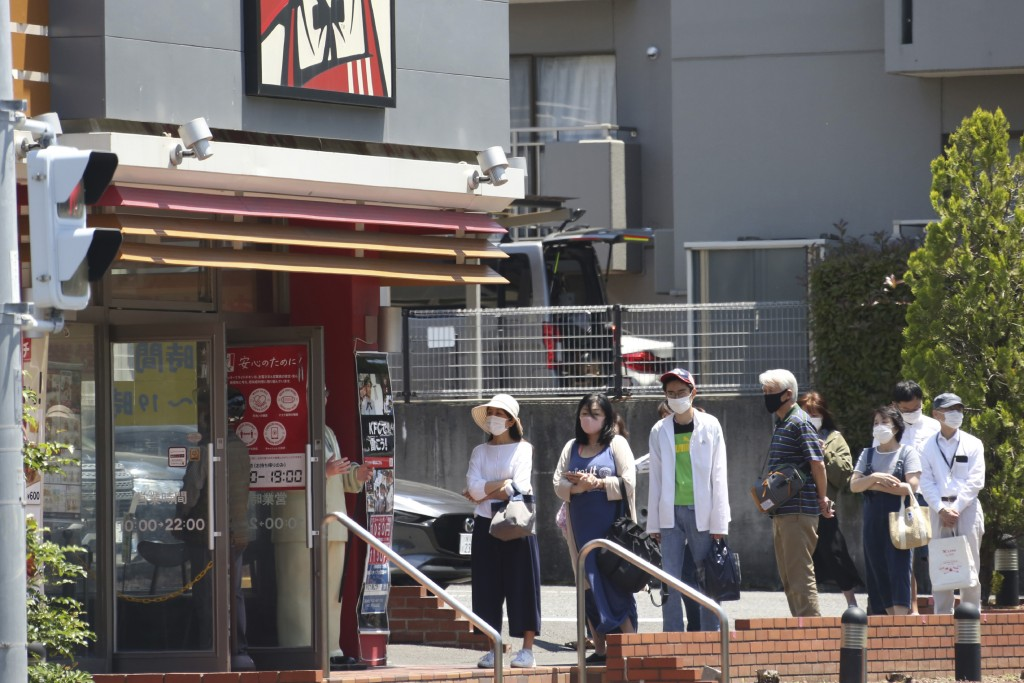 People wearing face masks to protect against the spread of the new coronavirus keep social distancing as they wait to enter a KFC restaurant in Yokoha...