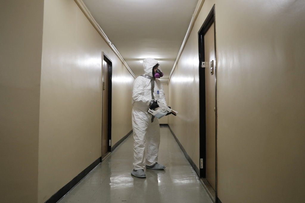 Safety Director Tony Barzelatto sprays disinfectant in a hallway of a building in Co-op City in the Bronx borough of New York, Wednesday, May 13, 2020...