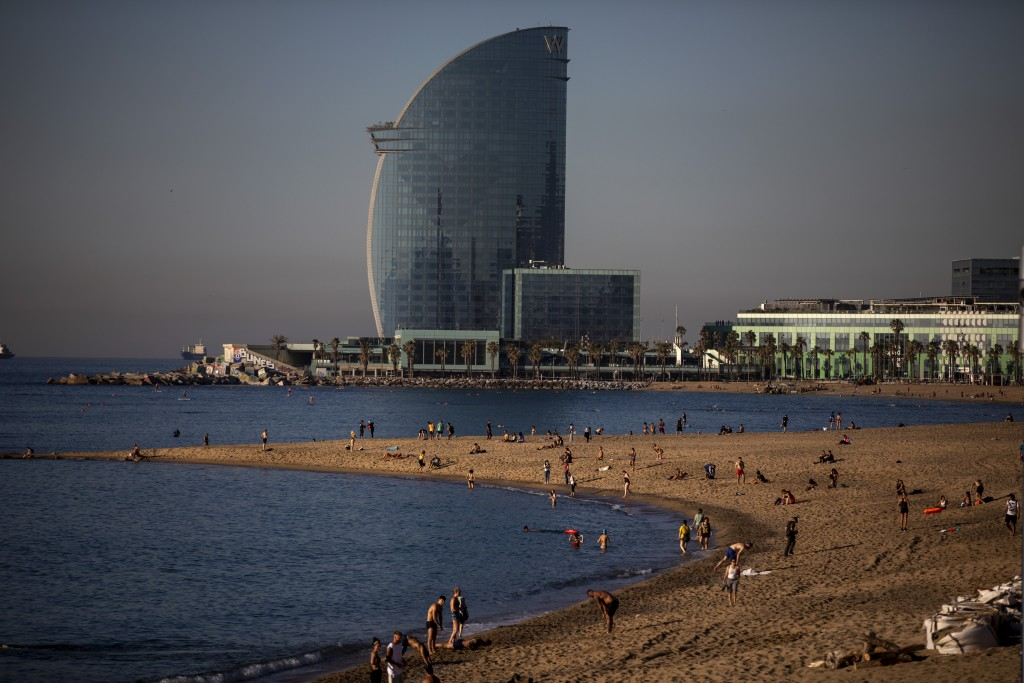 People enjoy the beach in Barcelona, Spain, Wednesday, May 20, 2020. Barcelona allowed people to walk on its beaches Wednesday, for the first time sin...