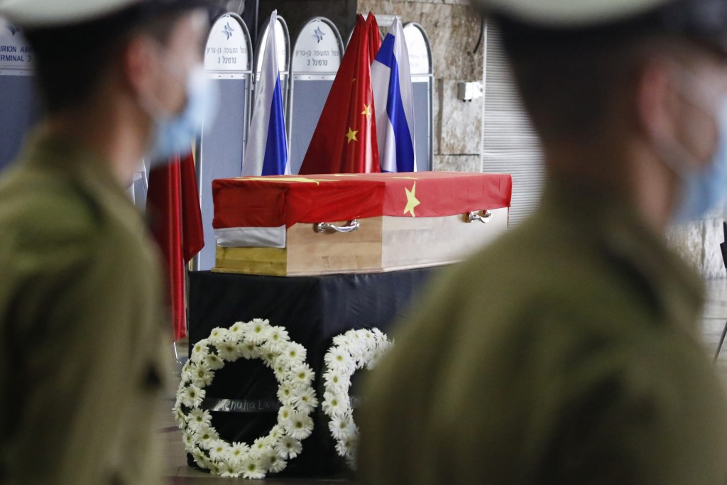 Mask-clad Israelis soldiers stand by the flag-draped coffin of Chinese Ambassador Du Wei, who died at his home in the coastal city of Herzliya, rests ...