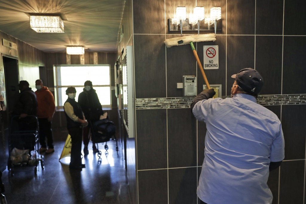 Residents watch as members of the janitorial staff wipe down the lobby of a building in Co-op City in the Bronx borough of New York, Wednesday, May 13...