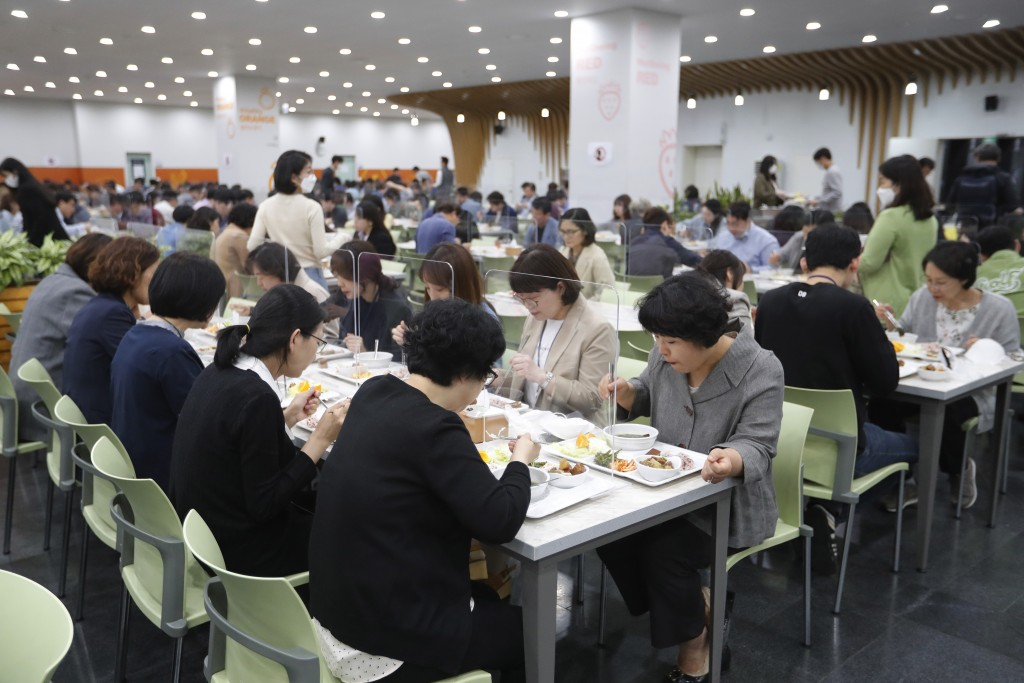 People eat lunch at tables equipped with plastic barriers to prevent any possible spread of the new coronavirus at the cafeteria of Seoul City Hall in...