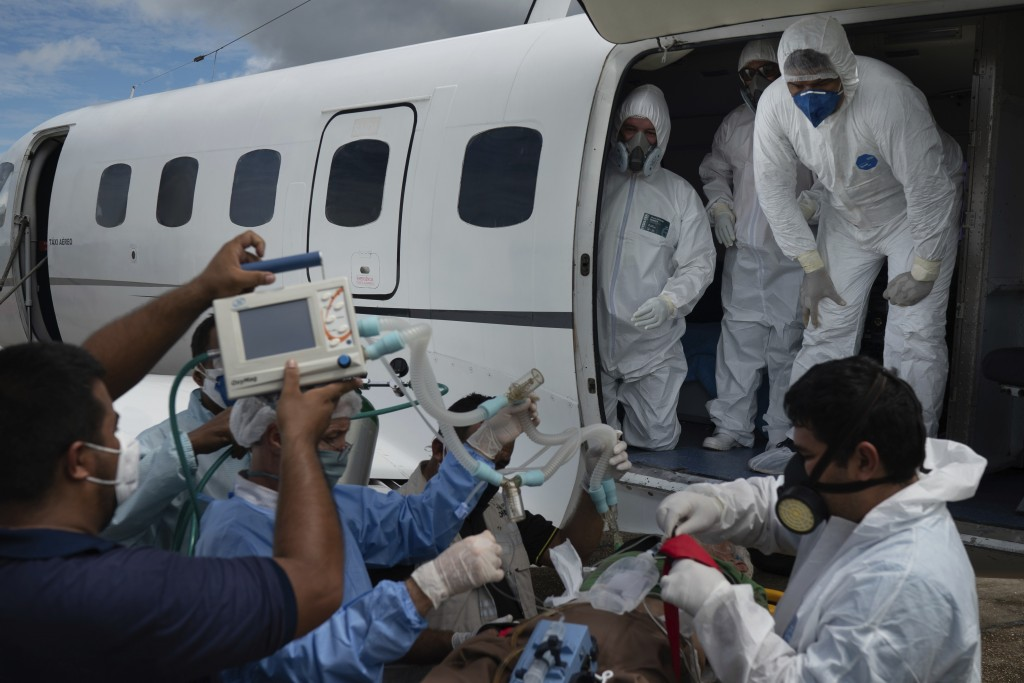 Health workers prepare to move 89-year-old COVID-19 patient Sildomar Castelo Branco into an aircraft as he is transferred from Santo Antonio do Içá to...