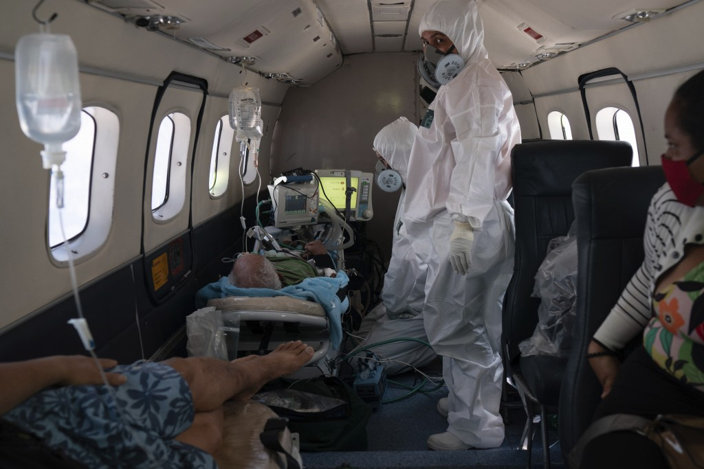Doctor Daniel Siqueira, center, and nurse Janete Vieira monitor COVID-19 patients onboard an aircraft as they are transferred from Santo Antonio do Iç...