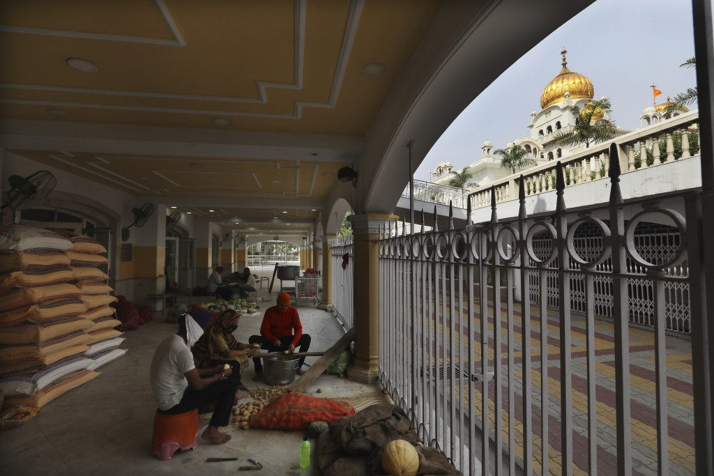 Sikh volunteers chop vegetables outside their kitchen hall at the Bangla Sahib Gurdwara in New Delhi, India, Sunday, May 10, 2020. The Bangla Sahib Gu...