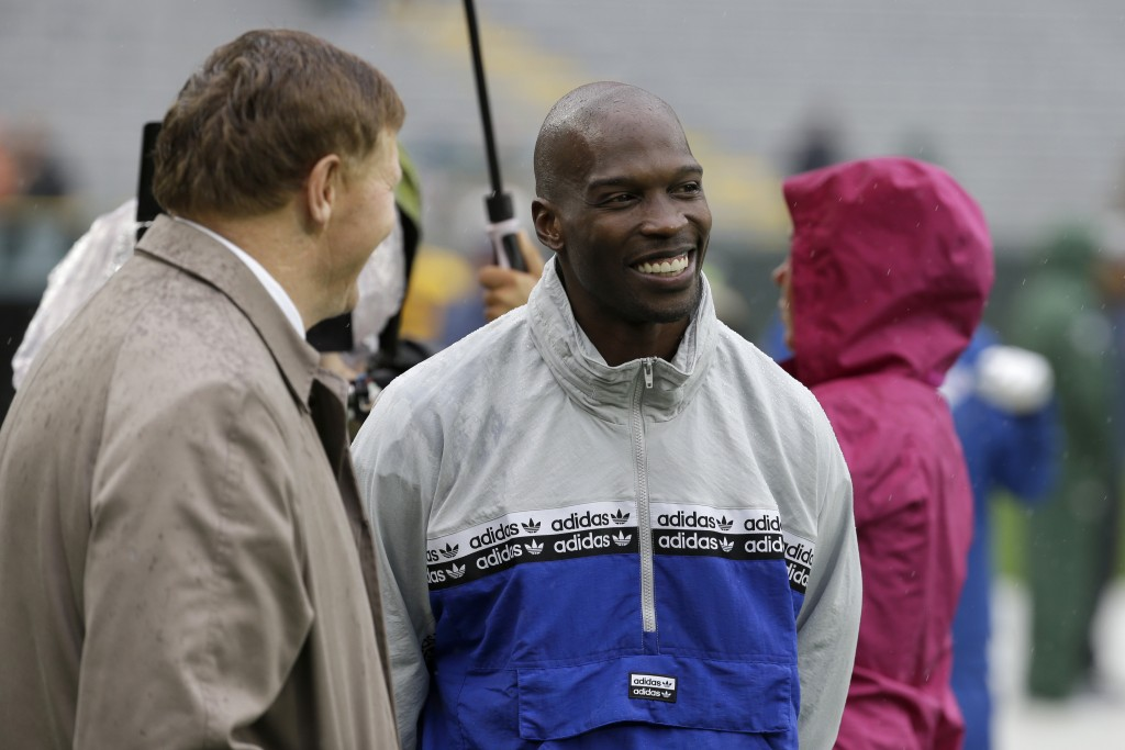 FILE - In this Sept. 22, 2019, file photo, former NFL football player player Chad Johnson, right, talks with Green Bay Packers president and chief exe...