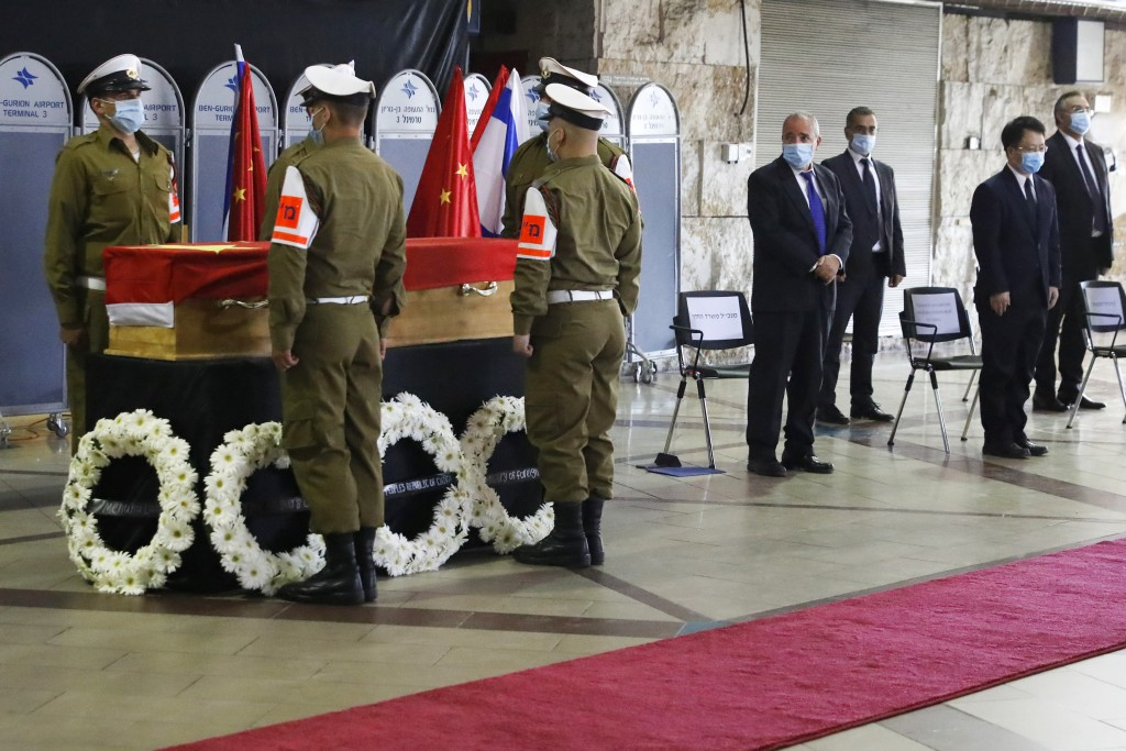 Mask-clad Israelis soldiers and officials stand near the flag-draped coffin of Chinese Ambassador Du Wei, who died at his home in the coastal city of ...