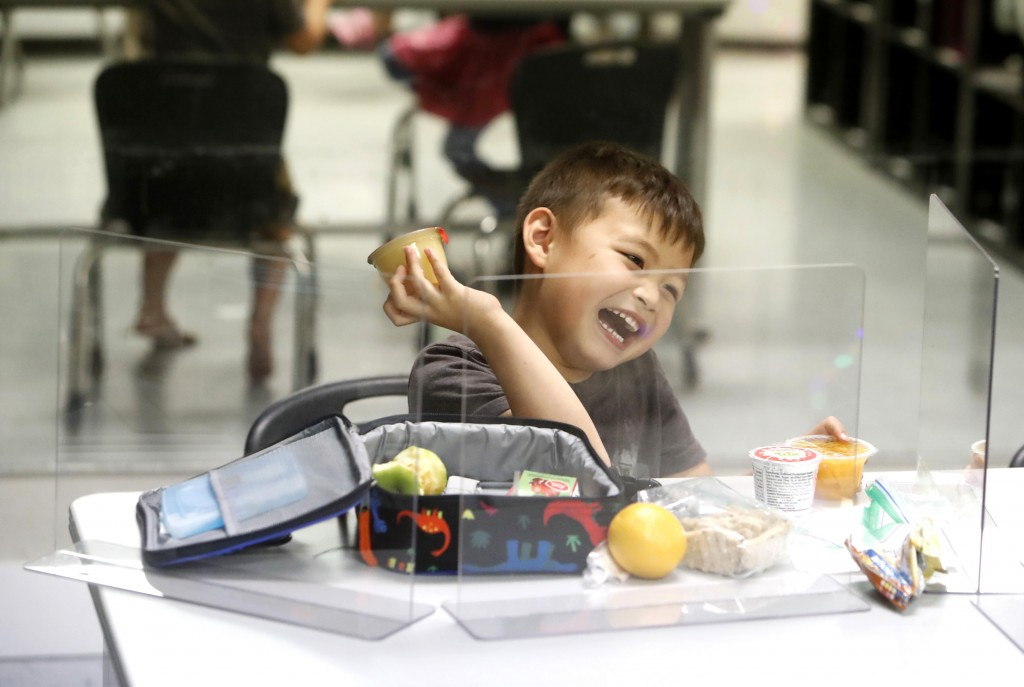 Bruce McCall, 5, laughs as he eats his lunch behind plastic barriers during martial arts daycare summer camp at Legendary Blackbelt Academy in Richard...