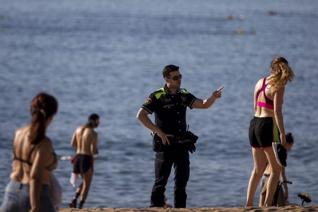 A police officer asks people to not sit while patrolling at the beach in Barcelona, Spain, Wednesday, May 20, 2020. Barcelona permitted Wednesday for ...