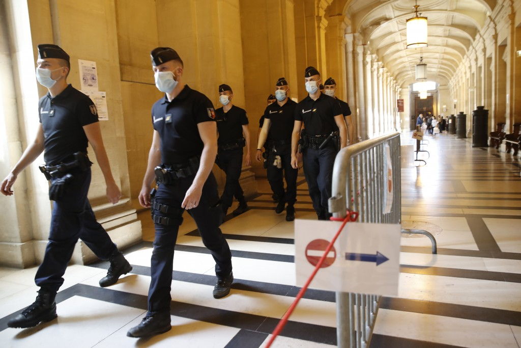 French gendarmes wear face masks in a gallery of the Hall of Justice Wednesday, May 20, 2020 in Paris as France gradually lifts its COVID-19 lockdown....