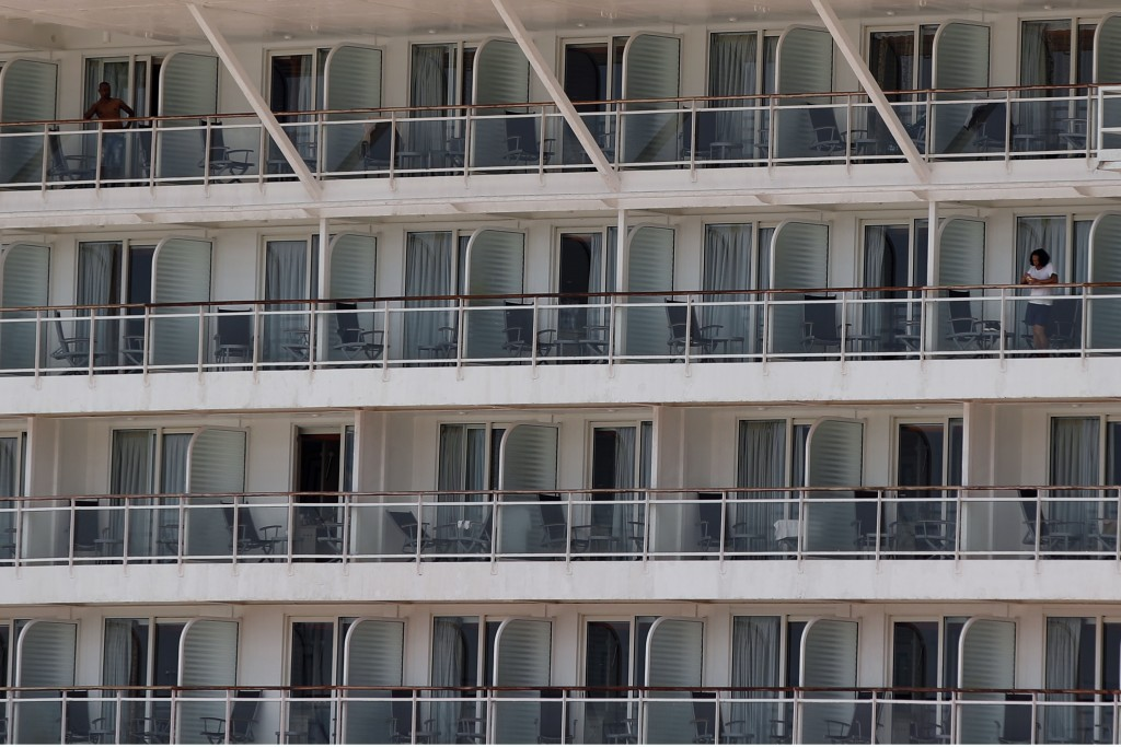 People stand on the balconies of their cabins, of a cruise ship that has been docked for almost two months due to the coronavirus outbreak at the port...