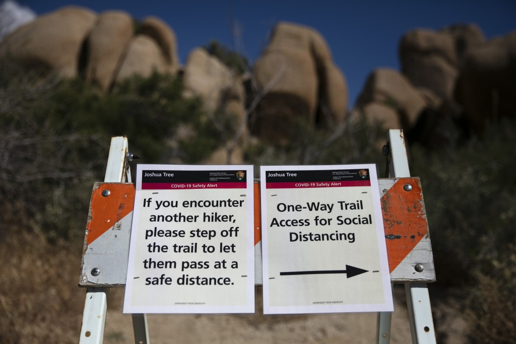 Signs advise visitors to social distance at Joshua Tree National Park in California, Tuesday, May 19, 2020. The park reopened this week after a length...