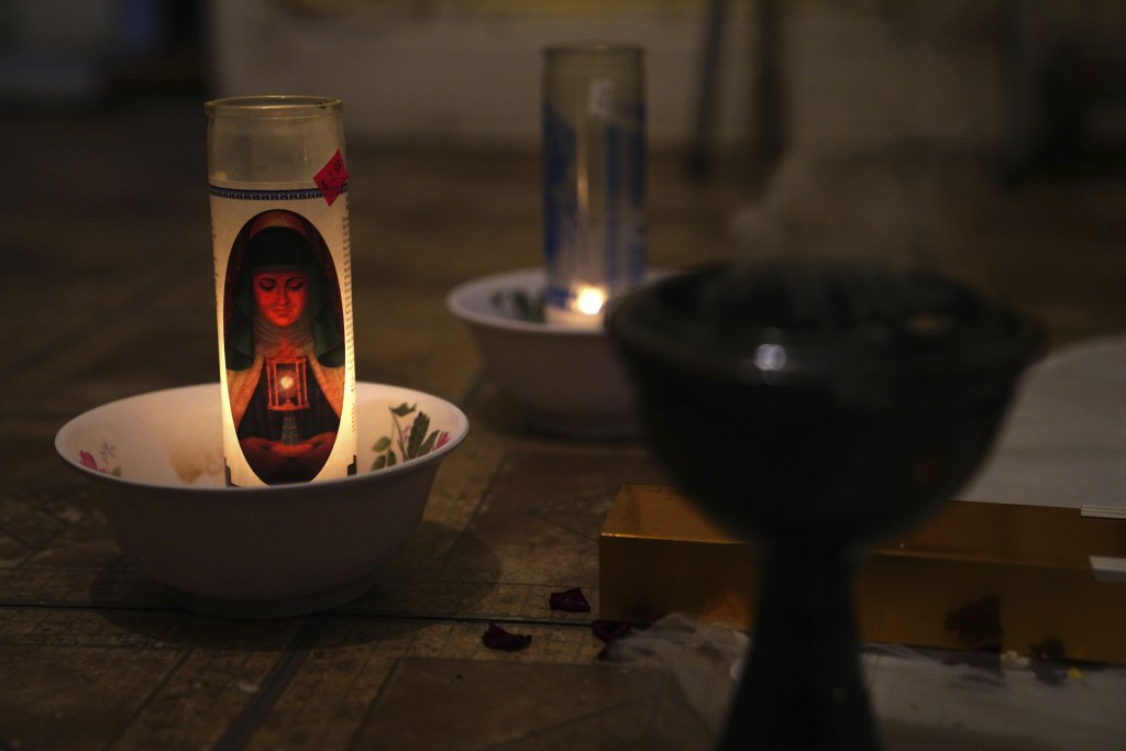 In this May 10, 2020 photo, a candle burns at a makeshift altar for Reyna Martinez's father, who died of COVID-19, in Martinez's home in the Queens bo...