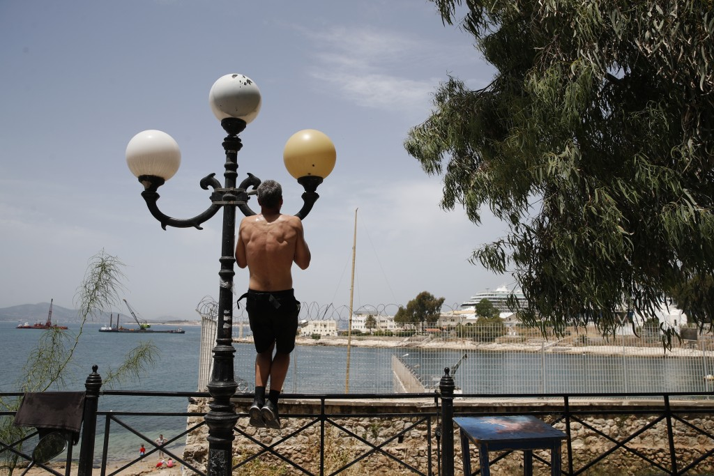 A man trains on a lighting column during a warm day in Piraeus, near Athens, Wednesday, May 20, 2020. Public beaches were reopened last weekend amid h...