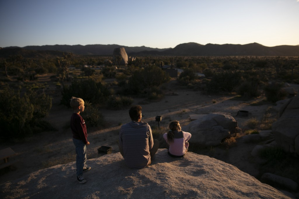 Aaron Stubbs and his two children sit on a rock to watch sunset at Joshua Tree National Park in California, Tuesday, May 19, 2020. The park reopened t...