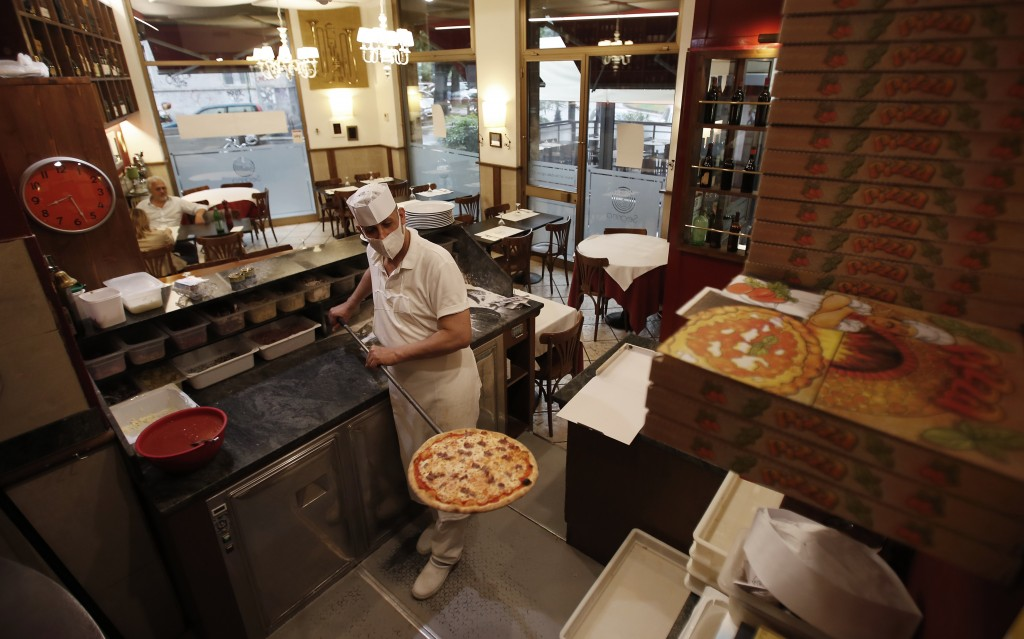 "Pizza maker Mimmo gets a pizza out of the oven at the ""La Rotonda di Segrino"" restaurant in Milan, Italy, Tuesday, May 19, 2020. On Monday, Italians e..."