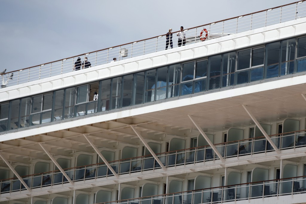 Crew members wearing face masks walk on the deck of a cruise ship that has been docked for almost two months due to the coronavirus outbreak at the po...