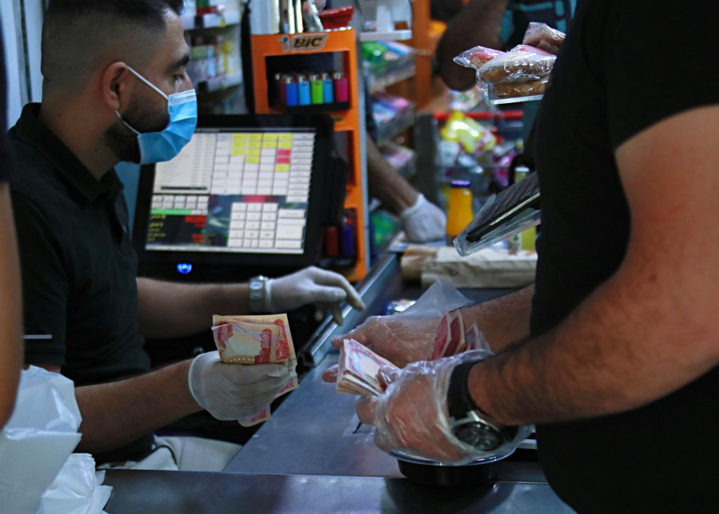 In this Sunday, May, 3, 2020, a man uses banknotes to pay for his purchases at a mall in Baghdad, Iraq. The coronavirus pandemic has reawakened debate...