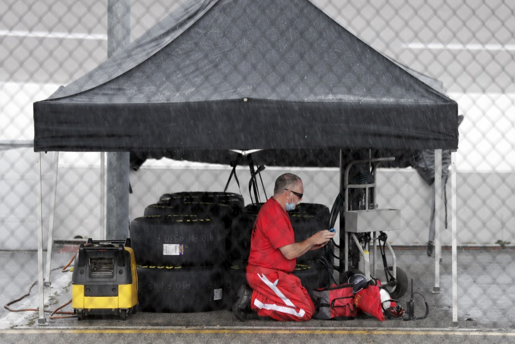 A crew member takes shelter under a tent as rain falls at the Darlington Raceway before the NASCAR Xfinity series auto race Tuesday, May 19, 2020, in ...