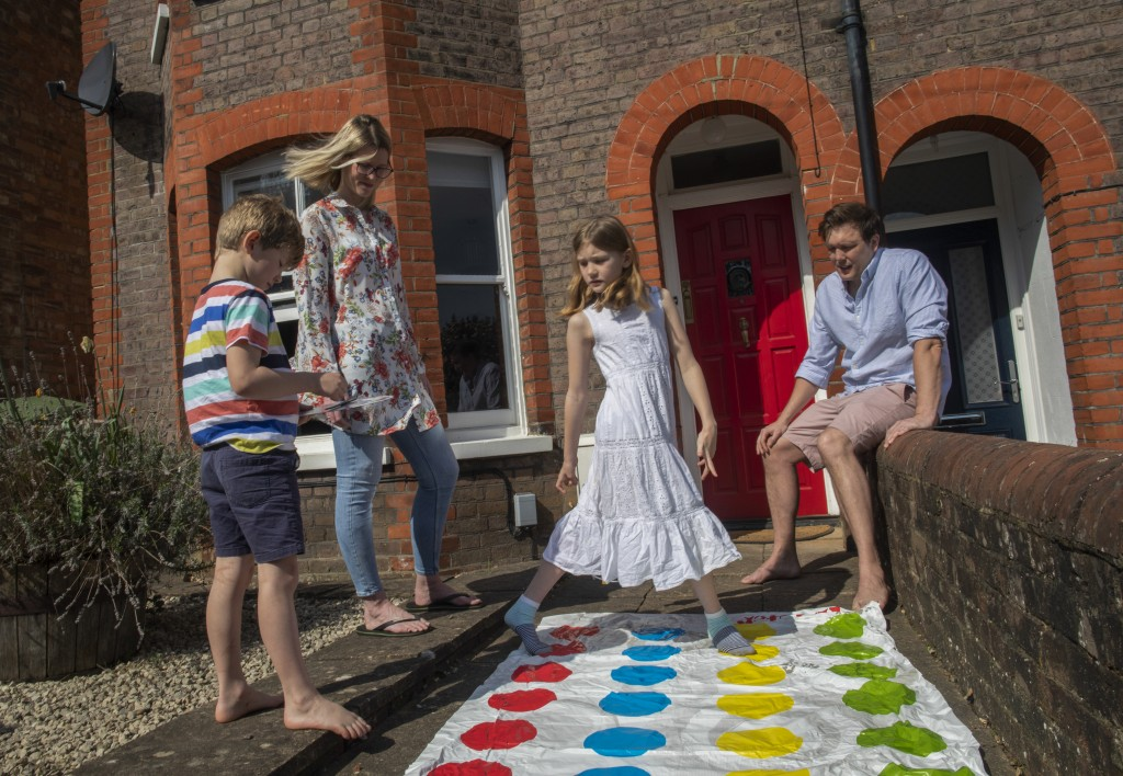 Kirsty, husband Dennis, Sophie, 8, and George, 6, enjoy a Carlton family favorite game of Twister in Berkhamsted, England, Friday, April 10, 2020. (AP...