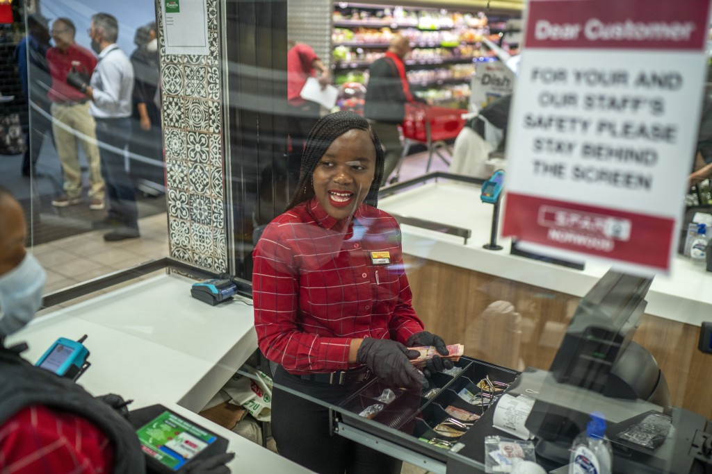 In this March 30, 2020, photo, Zandile Mlotshwa, 21, cashier at Spar supermarket in the Norwood suburb of Johannesburg, counts her cash at the end of ...