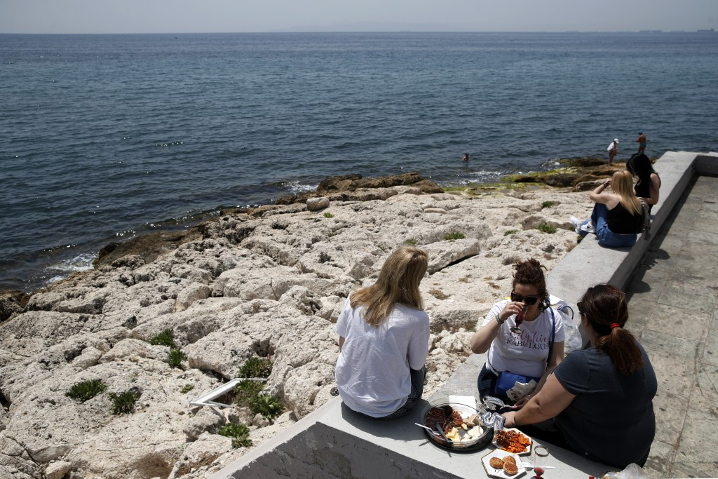 A company dining next to the sea during a warm day in Piraeus, near Athens on Wednesday, May 20, 2020. Public beaches were reopened last weekend amid ...