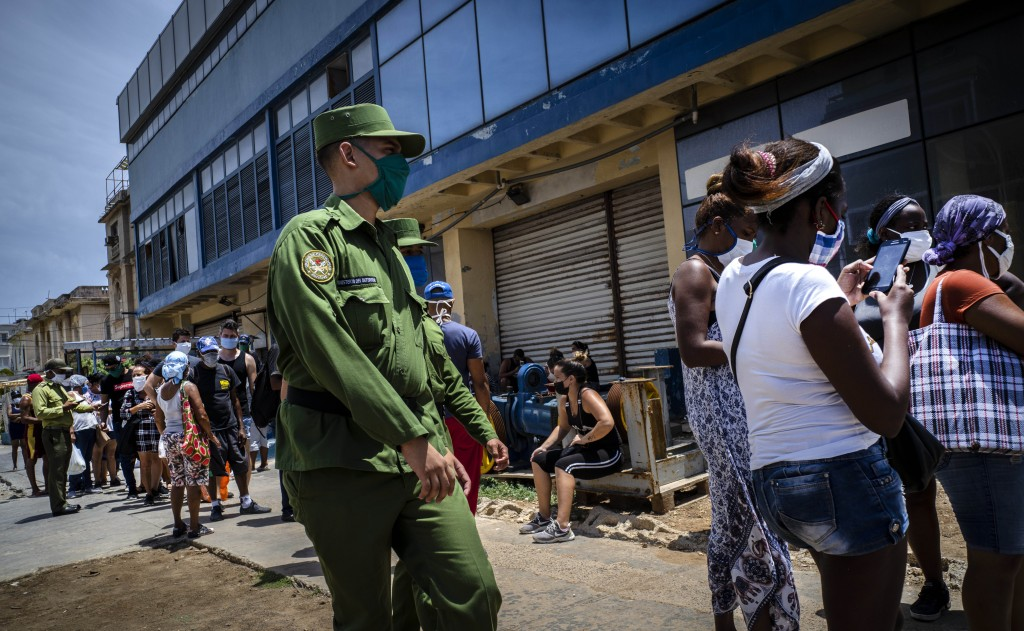 A soldier patrols outside a government-run food store where shoppers wait in line to enter in Havana, Cuba, Tuesday, May 19, 2020. State media has sta...