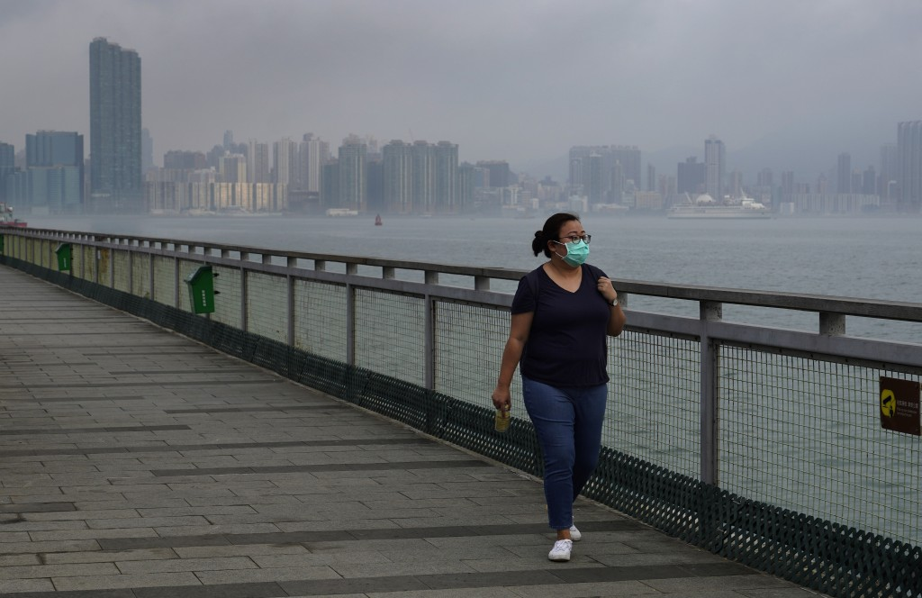 Associated Press reporter Zen Soo walks along the Quarry Bay Promenade in Hong Kong on the first day of freedom after 14 days of home quarantine in Ho...