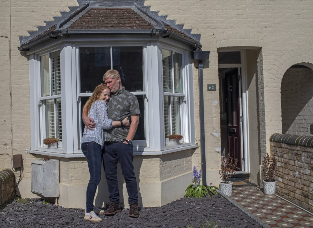 Catherine and Lloyde embrace in Berkhamsted, England, Wednesday, April 15, 2020. The couple are happy to be reunited after a long month separation whe...