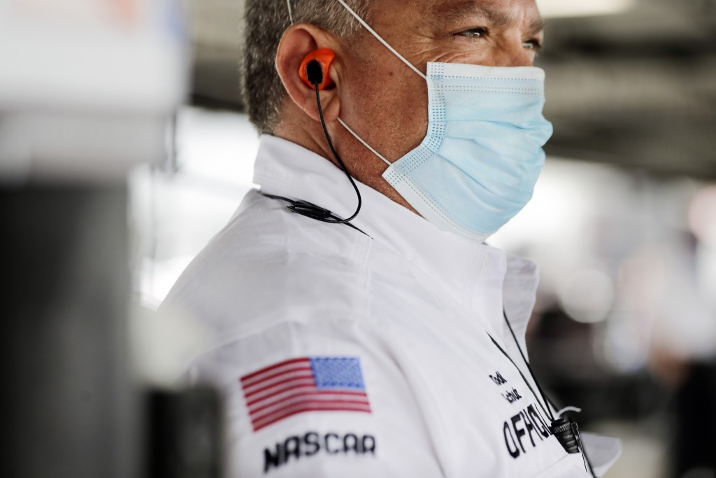 A NASCAR official wears a face mask because of the coronavirus pandemic as he works inside the garage before the NASCAR Xfinity series auto race Tuesd...