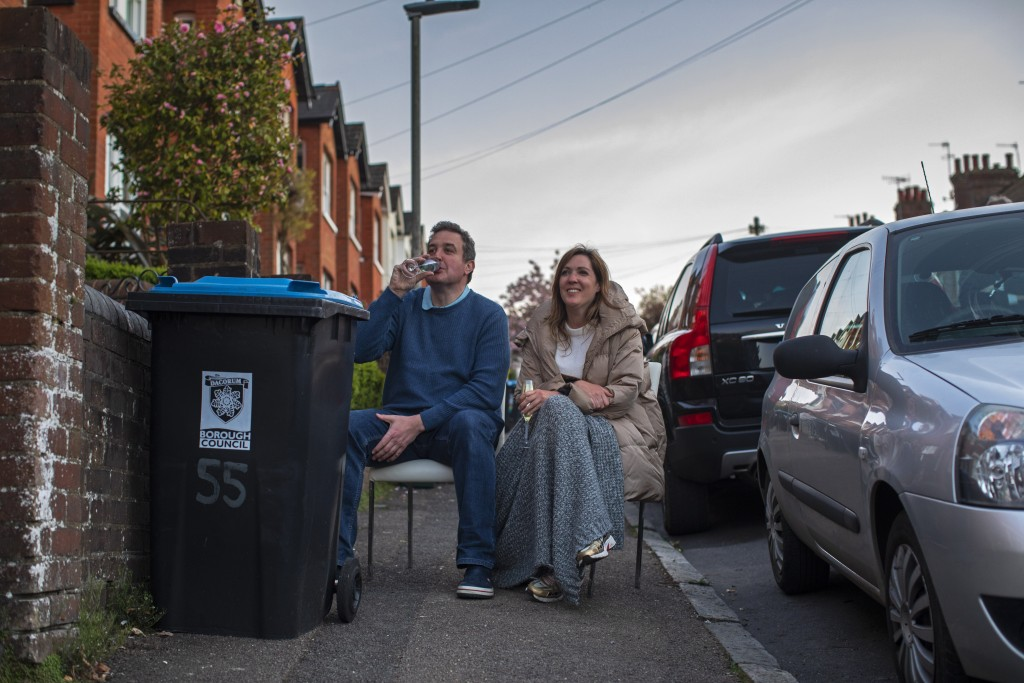 Jenny and Rob Kelly sip wine next to their recycling bin as they enjoy an impromptu cello concert from their neighbor outside their home in Berkhamste...