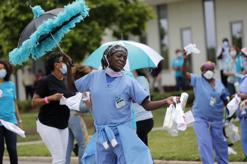 Healthcare workers at New Orleans East Hospital wave handkerchiefs and dance to a jazz serenade, as a tribute for their care for COVID-19 patients, by...