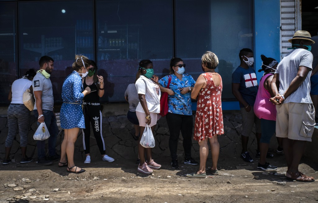 People wearing face masks amid the spread of the new coronavirus visit while waiting to enter a government-run food store in Havana, Cuba, Tuesday, Ma...