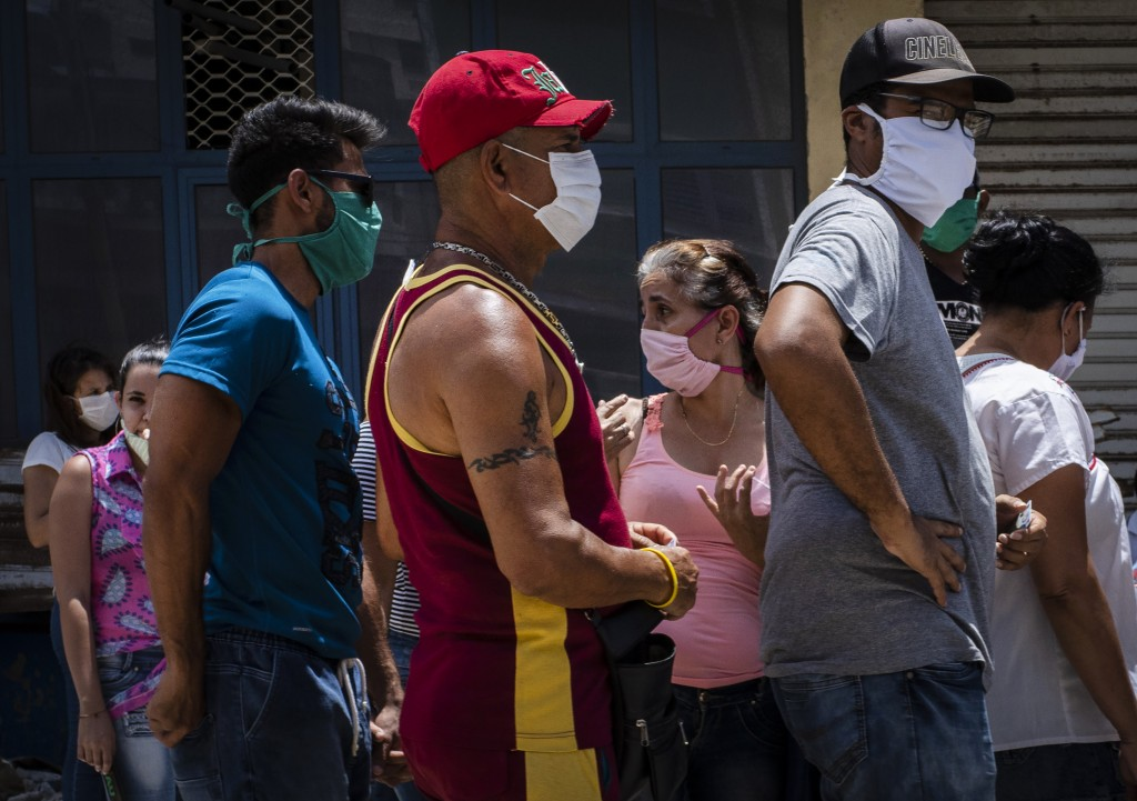 People wearing face masks amid the spread of the new coronavirus wait to enter a government-run food store in Havana, Cuba, Tuesday, May 19, 2020. Sta...