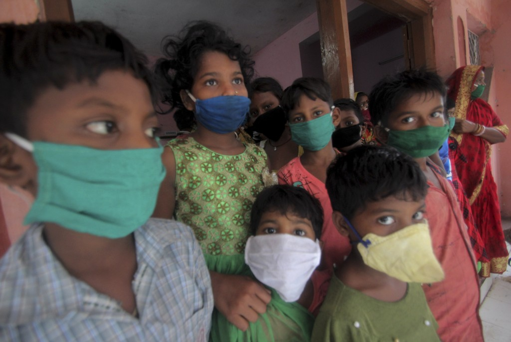 Evacuated children wearing masks as a precaution against the spread of coronavirus stand at a relief camp at Paradeep, on the Bay of Bengal coast in O...