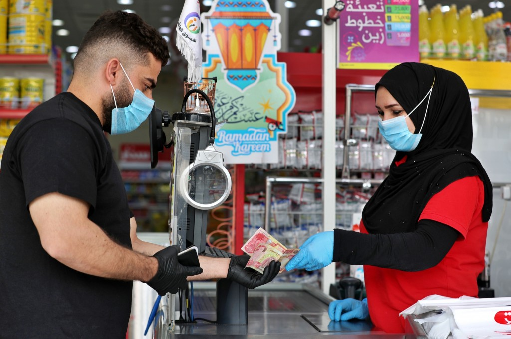 In this Saturday, May, 2, 2020, photo, a man uses banknotes to pay for his purchases at the mall in Basra, Iraq. The coronavirus pandemic has reawaken...