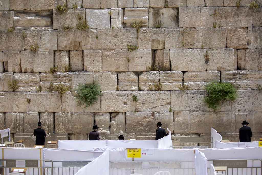 Men keep social distance while pray at the Western Wall, the holiest site where Jews can pray in Jerusalem's old city, Tuesday, May 19, 2020. Israeli ...