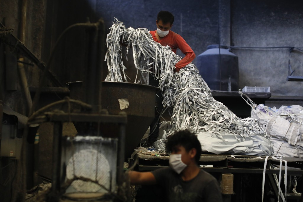 Paola Ventura, top, feeds plastic waste into a machine to be melted and reformed, at the Alexis Plastics factory in Ecatepec, Mexico, Tuesday, May 19,...