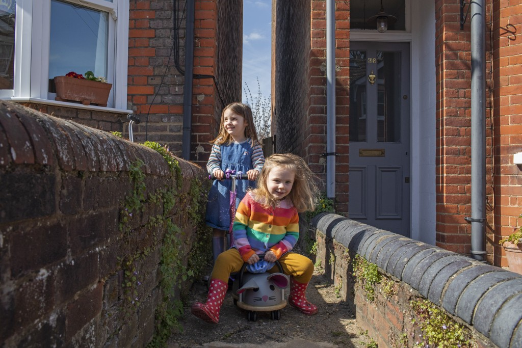 Astrid 5, and Martha 3, enjoy a scoot along their home's alley and a little freedom during the Easter holidays in Berkhamsted, England, Tuesday, April...