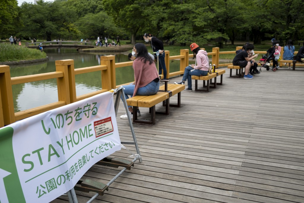 Park goers gather at Yoyogi Park in Tokyo Friday, May 15, 2020. In this country driven by conformity and consensus, the pandemic is pitting those will...