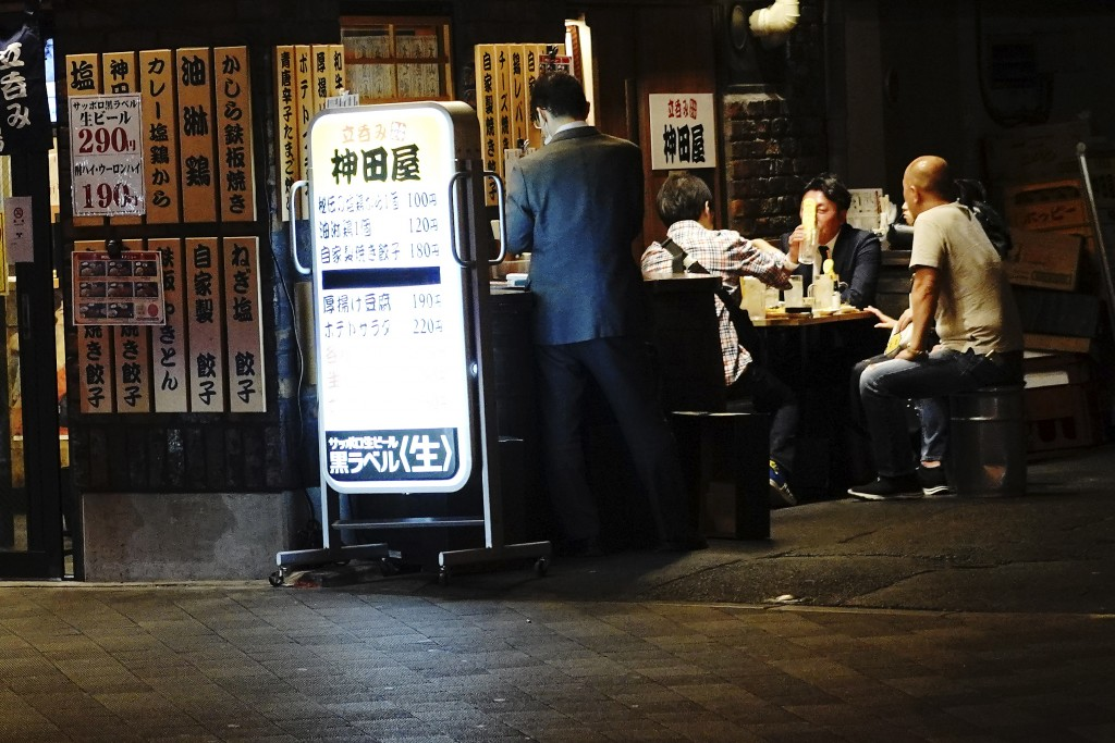 People drink at a bar in Tokyo Thursday, May 14, 2020. While Tokyo is still under a coronavirus state of emergency, the pandemic is pitting those will...