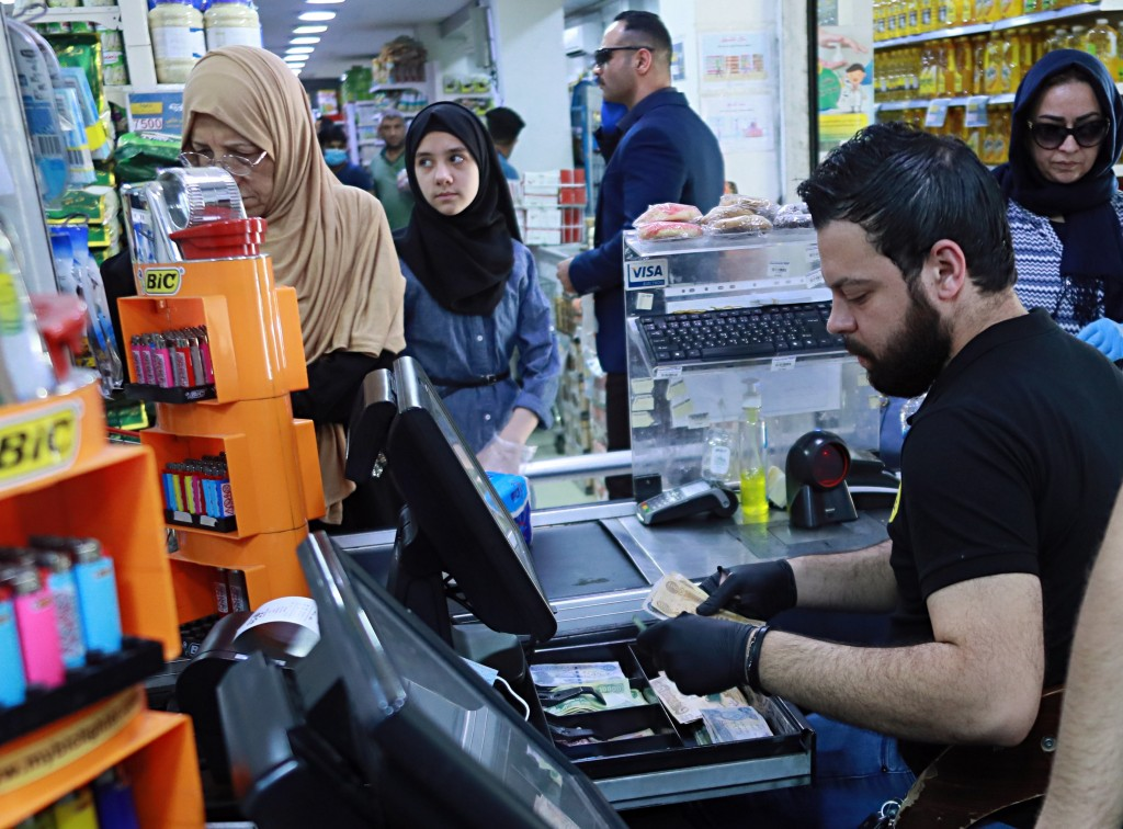In this May, 3, 2020, a casher holds Iraqi banknotes at a mall in Baghdad, Iraq. The coronavirus pandemic has reawakened debate about the continued vi...