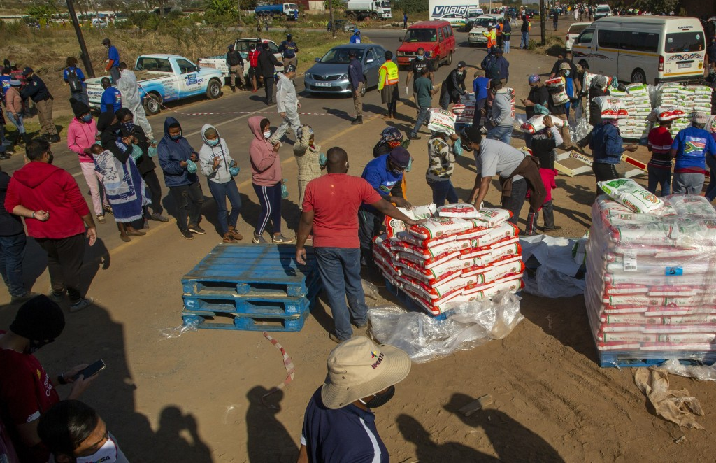 People affected by the coronavirus economic downturn, receive food donations at the Iterileng informal settlement near Laudium, southwest of Pretoria,...